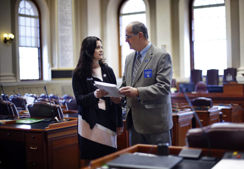 Republican state Reps. Amy Arata and her father, Richard Bradstreet, discuss legislation Thursday in the House chamber at the State House in Augusta. State records compiled by Maine's legislative library suggest they're the first father and daughter to serve as legislators together in Maine history. But they're not the first pair nationwide.