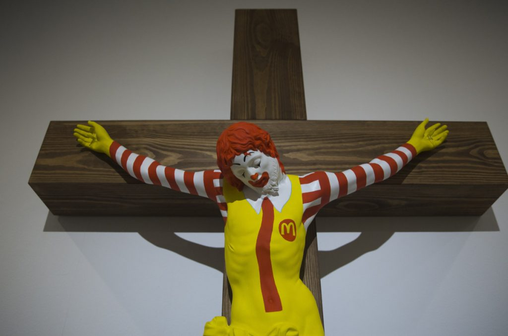 """An artwork called """"McJesus,"""" which was sculpted by Finnish artist Jani Leinonen and depicts a crucified Ronald McDonald, is on display as part of the Haifa museum's """"Sacred Goods"""" exhibit."""
