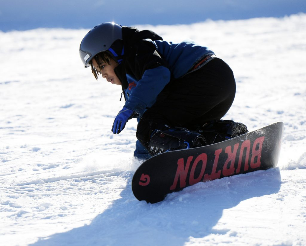 Nehemiah Suneus, 10, of the Boys & Girls Club of Dorchester, Mass., concentrates as he learns to snowboard at Shawnee Peak last weekend. Suneus was snowboarding for the first time and picked it up in 10 minutes.