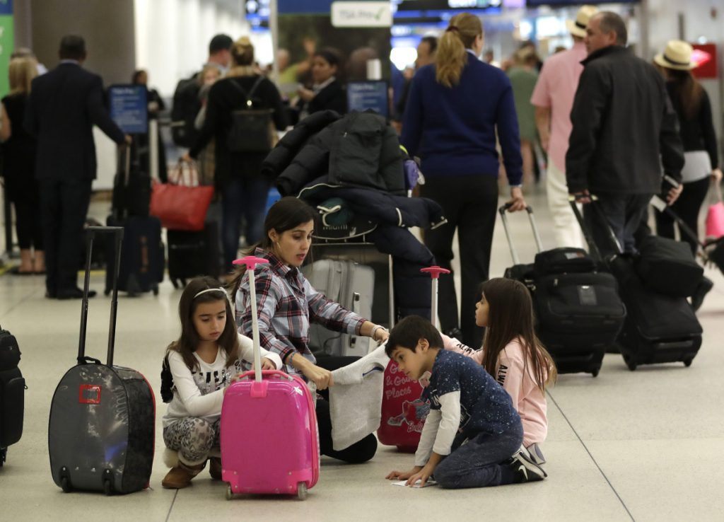 Travelers organize their luggage before entering a security checkpoint at Miami International Airport on Friday. The three-day holiday weekend – one with inclement weather in the forecast –is likely to test the nation's air-travel system as the partial government shutdown enters its fifth week.