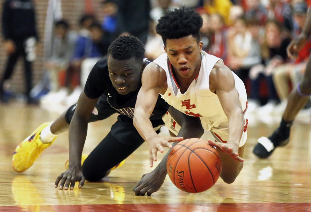 Loki Anda of Deering, left, and Tyree Bitjoka of South Portland scramble for a loose ball Friday night during Deering's 50-41 victory at Beal Gym. Deering beat the Red Riots for the second time this season.