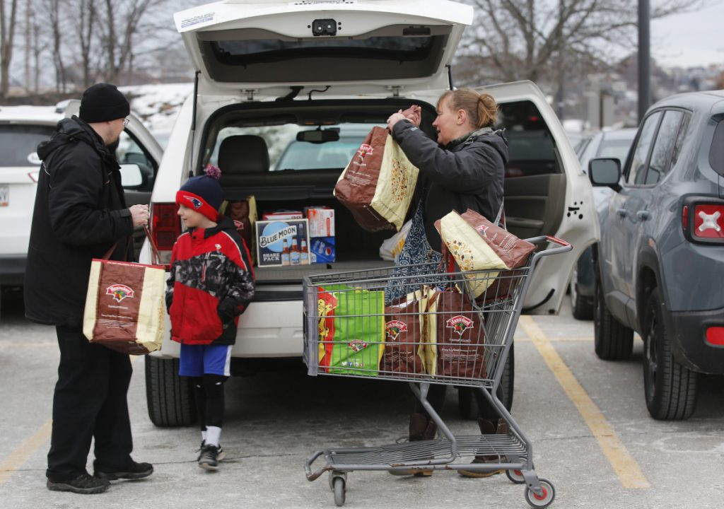 Damien Pierce, 7, waits as his parents, Loree and Nick, load groceries at the Hannaford supermarket in Portland on Saturday. The family was stocking up for the Patriots game.