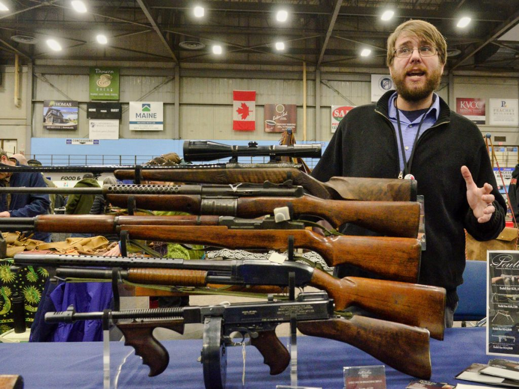Dave Hayward, of Poulin Antiques and Auctions, talks about antique rifles on display during a gun show Saturday at the Augusta Civic Center.