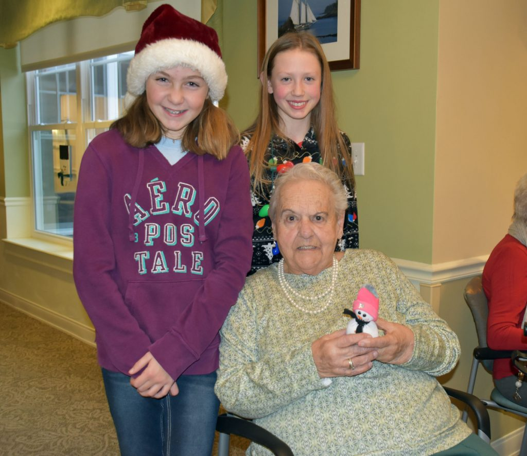 Avita resident Rose Fawcett receives a homemade snowman from Wells Junior High School students Teagan Hludik, left, and Molly Tavares.