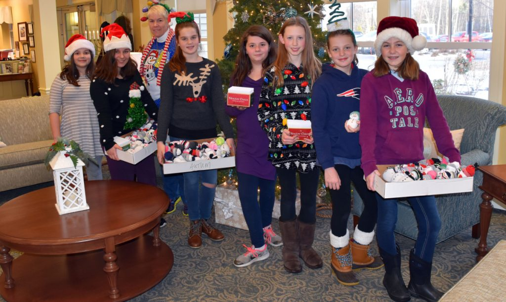 Wells Junior High School students make a holiday visit to Avita of Wells to deliver handmade snowmen and personalized greeting cards to 68 residents. The visit was part of the school's service learning project. From left, students Melody Goodwin and Belle Norton, Renèe Savage, and students Logan Blanchard, Catie Kasabinski, Molly Tavares, Jessica Palmer and Teagan Hludik.
