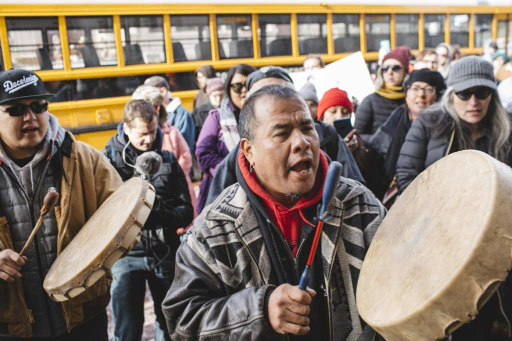 Sleepy Eye LaFromboise, left, beats a drum outside the Covington Catholic Diocese on Tuesday, while a member of a motorcycle club that backs President Trump talks with Native Americans in support of the students.