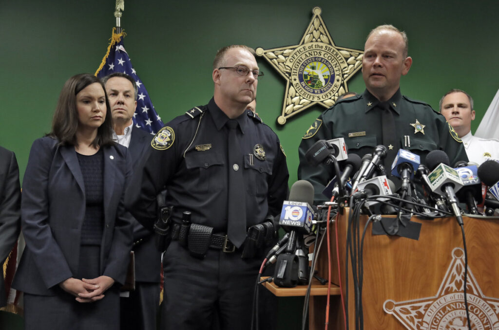 Highlands County Sheriff Paul Blackman, right, speaks to the media as he stands with Florida Attorney General Ashley Moody, left, and Sebring Police Chief Karl Hoglund, center, during a news conference on Thursday in Sebring, Fla. Five people were shot and killed Wednesday at a SunTrust Bank.