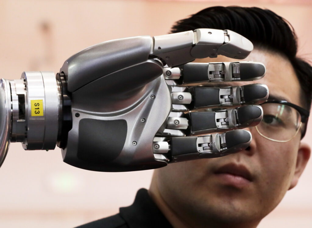 A visitor inspects a robotic hand at the World Robot Conference in Beijing in 2017. A Brookings Institution study suggests workplace automation will continue to displace U.S. workers.