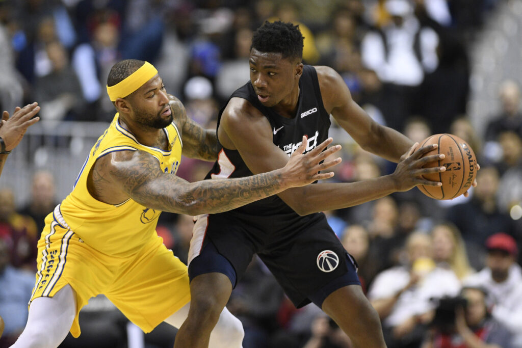 Golden State's DeMarcus Cousins reaches for the ball against Washington center Thomas Bryant in the first half of Thursday's game at Washington.