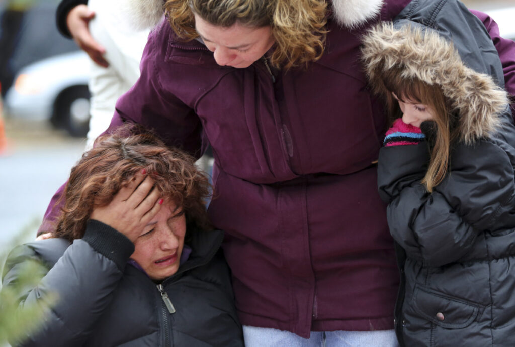 Mourners grieve in 2012 after the shootings at Sandy Hook Elementary School in Newtown, Conn., which killed 26 people. Three more mass shootings during the 2017-18 school year killed 29 people – in Florida, Texas and New Mexico.