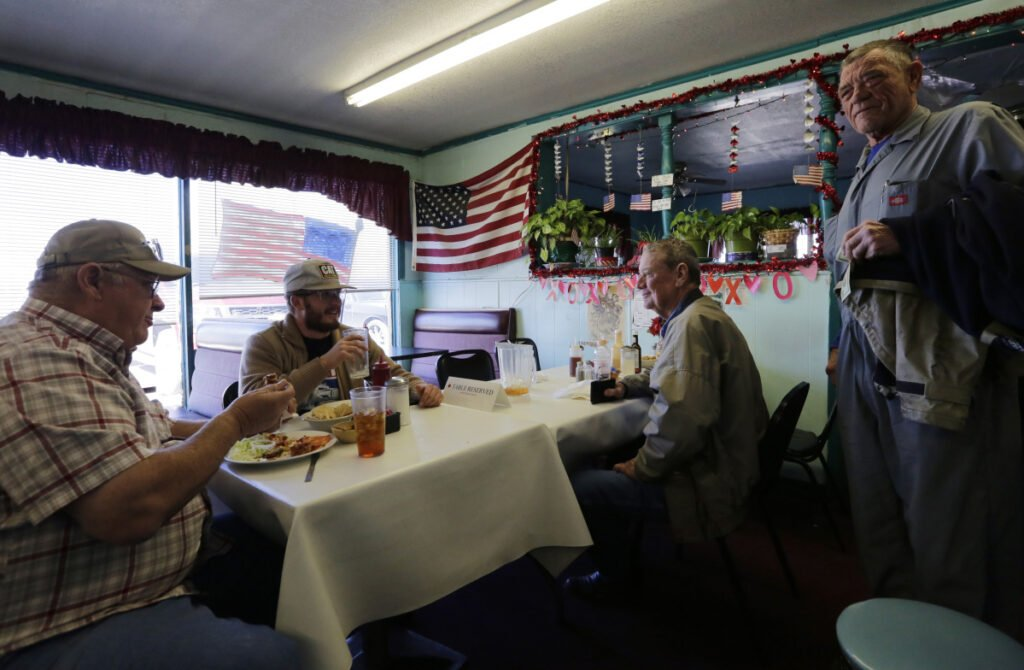 Gene Henderson, from left, Brandon Henderson and Terry Rose, right, have lunch at Angie's Cafe in Fort Hancock, Texas. Gene Henderson, a 69-year-old Vietnam veteran and retired Border Patrol agent who now has a small farm, said the government shutdown could cement President Trump's 2020 re-election.