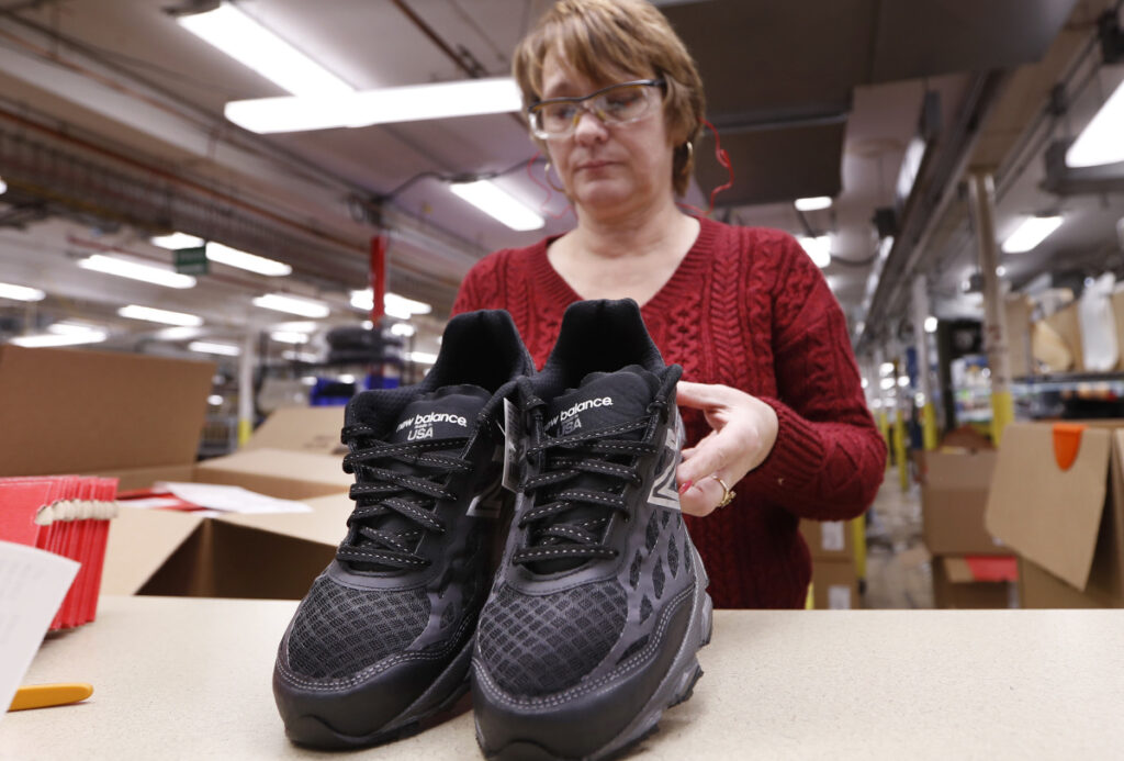 Ruby Williams inspects a pair of sneakers designed for the military at the New Balance factory in Norridgewock.