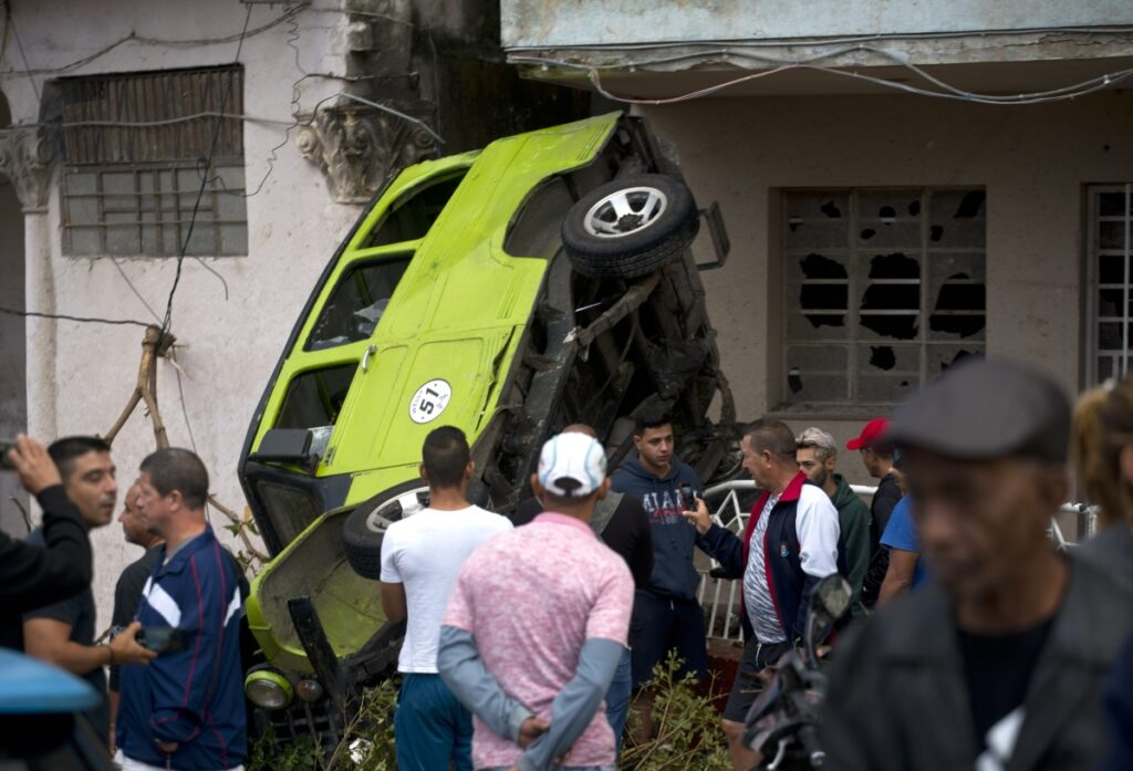 People stand around a car that was overturned by a tornado in Havana, Cuba, Monday. A tornado and pounding rains smashed into the eastern part of Cuba's capital overnight, toppling trees, bending power poles and flinging shards of metal roofing through the air as the storm cut a path of destruction.