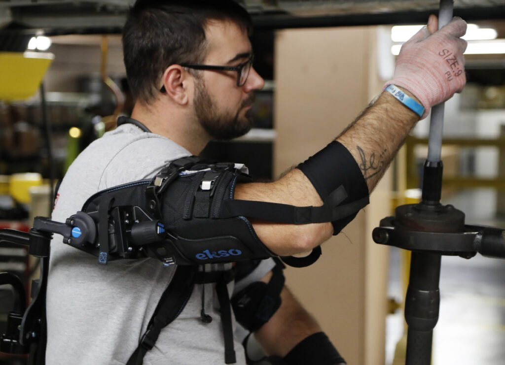 Ford assembly line worker Nicholas Gotts wears a new wearable technology called an EksoVest.