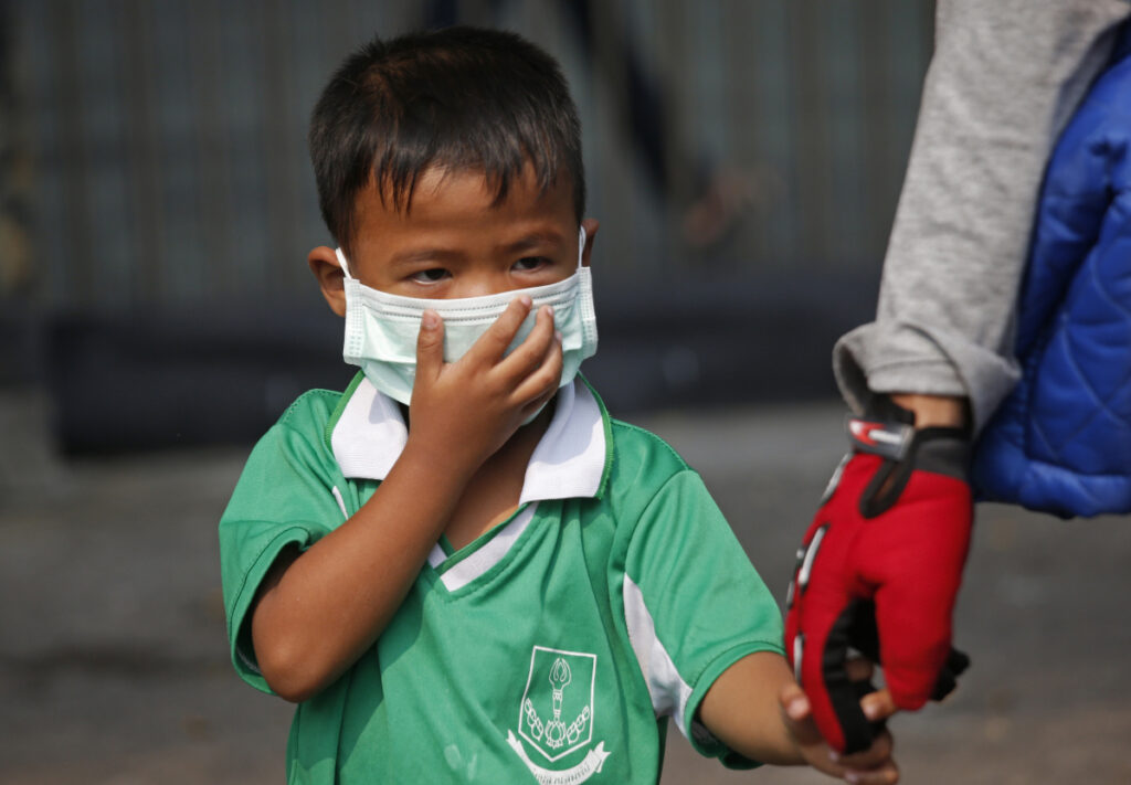 A young boy wears a protective mask for the high levels of air pollution as he's picked up from school in Bangkok, Thailand, on Wednesday