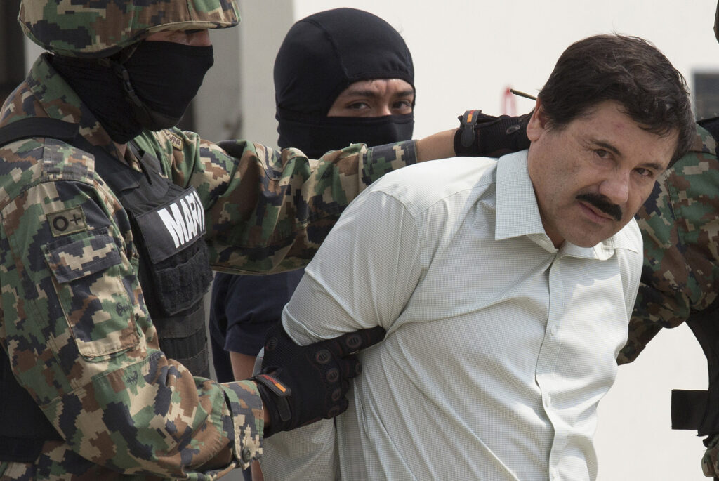 "Joaquin ""El Chapo"" Guzman is escorted to a helicopter by Mexican security forces at Mexico's International Airport in Mexico city, Mexico, on Feb. 22, 2014. MUST CREDIT: Bloomberg photo by Susana Gonzalez"
