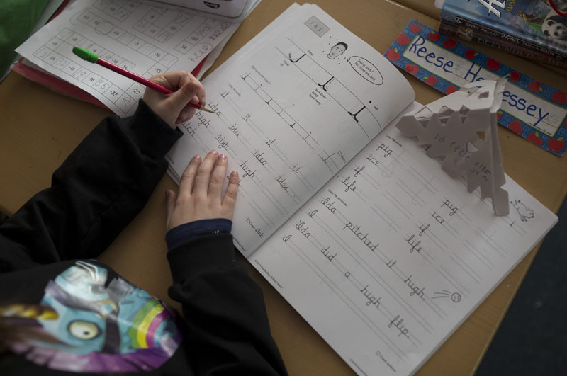 "Reese Hennessey practices cursive words with the letter ""i"" in them in Tracy Burns' class at Narragansett Elementary School in Gorham in December."