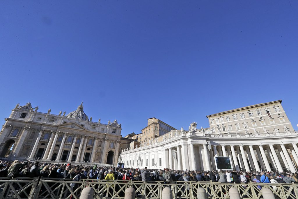 People gather in St. Peter's Square to attend a blessing by Pope Francis during the Angelus noon prayer he recited from the window of his studio at the Vatican on Tuesday.