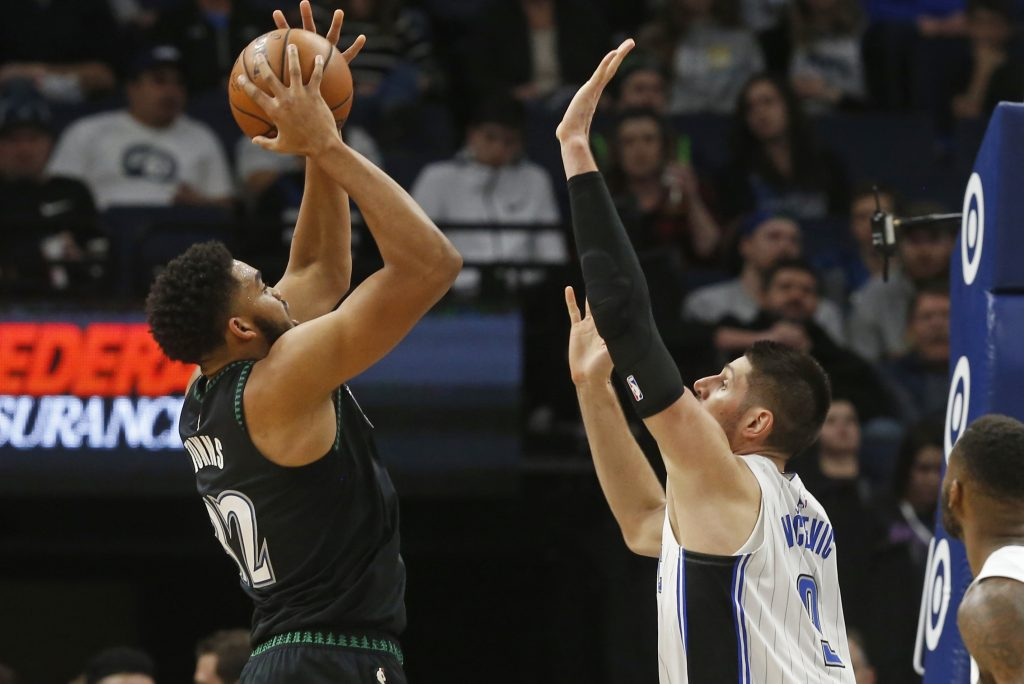 Minnesota Timberwolves' Karl-Anthony Towns, left, shoots over Orlando Magic's Nikola Vucevic during the Timberwolves 120-103 win Friday in Minneapolis.