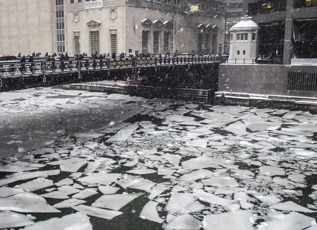 Pedestrians cross an icy Chicago River on Madison St. near the Civic Opera House in Chicago, Monday, Jan. 28, 2019.