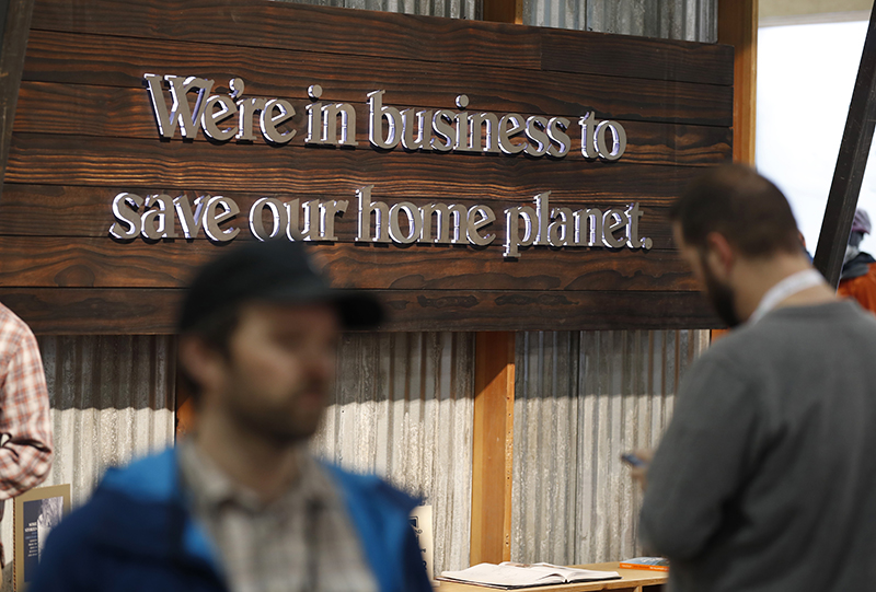 Buyers pass by a sign in the Patagonia exhibit at the Outdoor Retailer & Snow Show in the Colorado Convention Center in Denver on Wednesday.