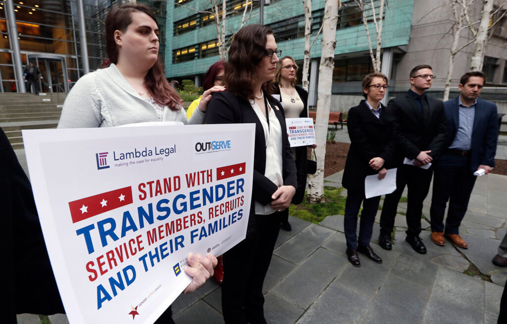 Plaintiffs Cathrine Schmid, second left, and Conner Callahan, second right, listen with supporters during a news conference in front of a federal courthouse following a hearing in Seattle on March 27, 2018. Transgender-rights activists were angered at moves by President  Trump and his administration to undermine gains achieved before his election. Trump is seeking to ban transgender people from military service.