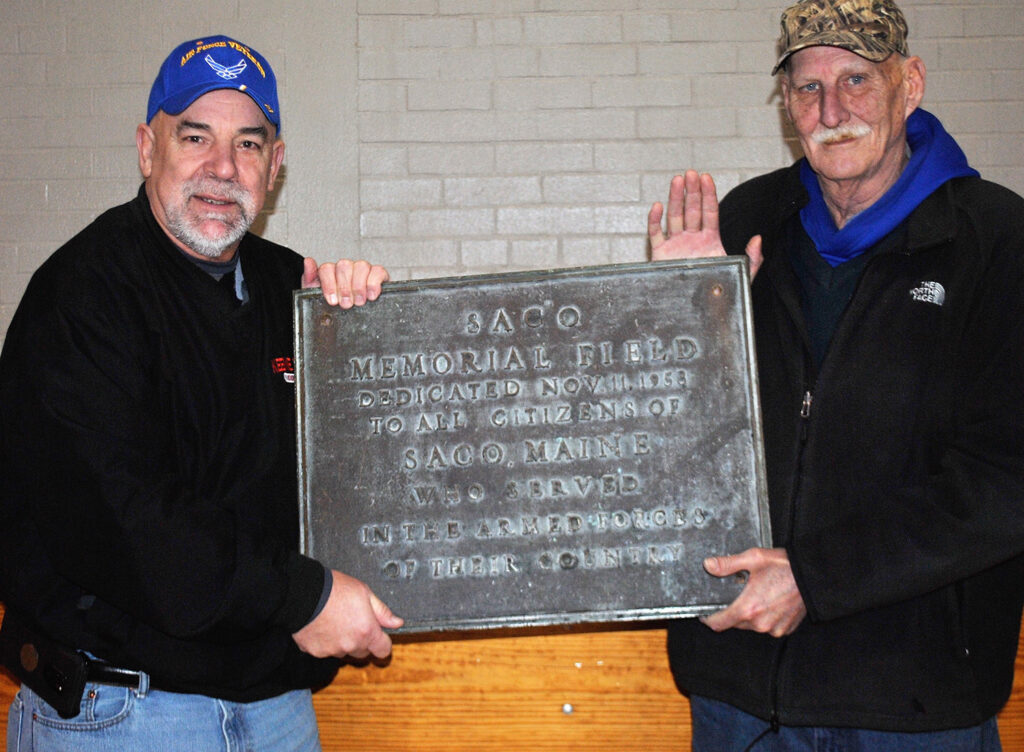 Ron Kendall and Marty Feery of Wethersfield, Connecticut, hold the sign they returned to Saco at the Saco Community Center on Tuesday.