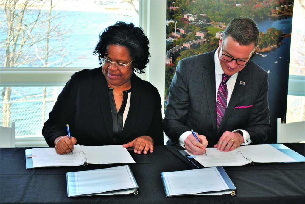 Danielle Conway, dean of the University of Maine School of Law, and University of New England President James Herbert sign an agreement between the two colleges Wednesday at the UNE campus in Biddeford.