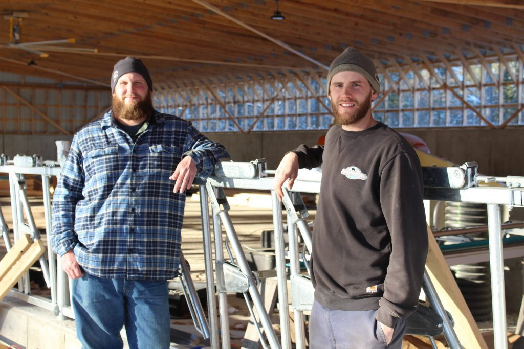 Dairy farmers Ben Jensen, left, and Matt DeGrandpre stand in one of several buildings that will make up the new dairy facility at Wolfe's Neck.