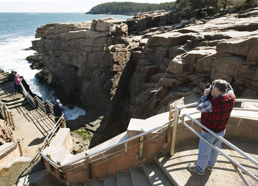 People visit the Thunder Hole along Ocean Drive in Acadia National Park in April 2016. After the 35-day partial government shutdown, park officials say they don't know if everything will open on time come spring.