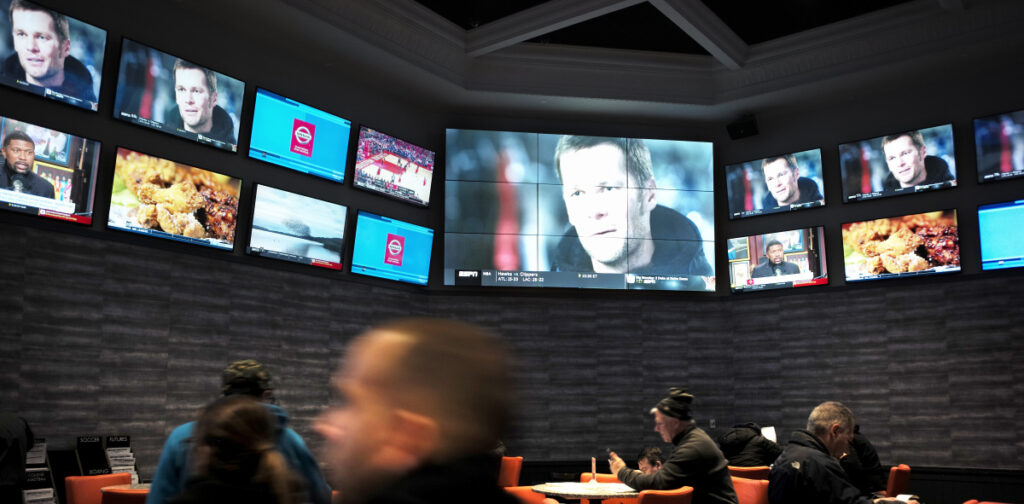 Patrons visit the sports-betting area of Twin River Casino in Rhode Island. The issue is the focus of a series of Maine bills this session.