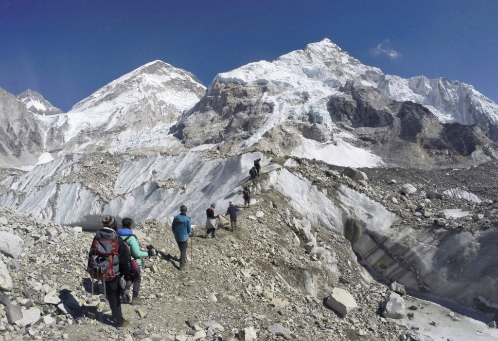 Trekkers pass through a glacier at the Mount Everest base camp, Nepal, on Feb. 22, 2016. A study reported one-third of Himalayan glaciers will melt by the end of the century due to climate change.