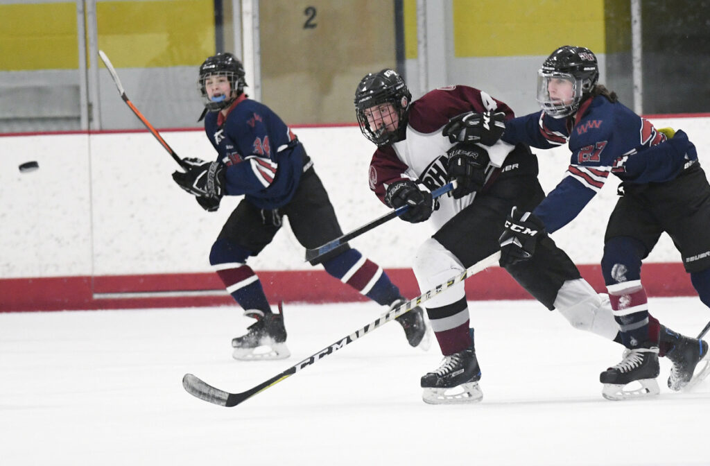 Peter Richards of Gorham drives the puck up the ice Tuesday in front of Jordan Cantz of Windham/Westbrook during Gorham's 9-1 victory. The Rams improved to 7-5 and dropped Windham to 1-10.