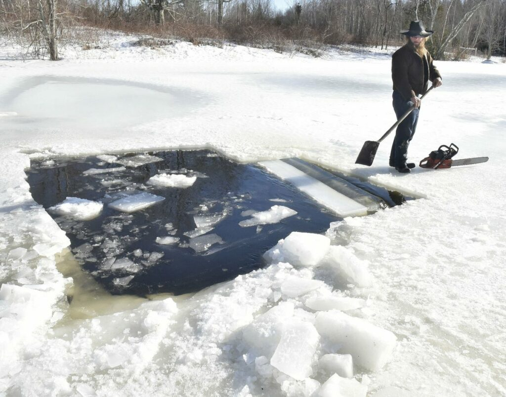 Amish farmer Isaac Hostetler separates with a shovel a large block of ice he cut from a pond at his farm in Palmyra on Wednesday. The ice will be used for an ice bar during Somerset SnowFest this weekend.