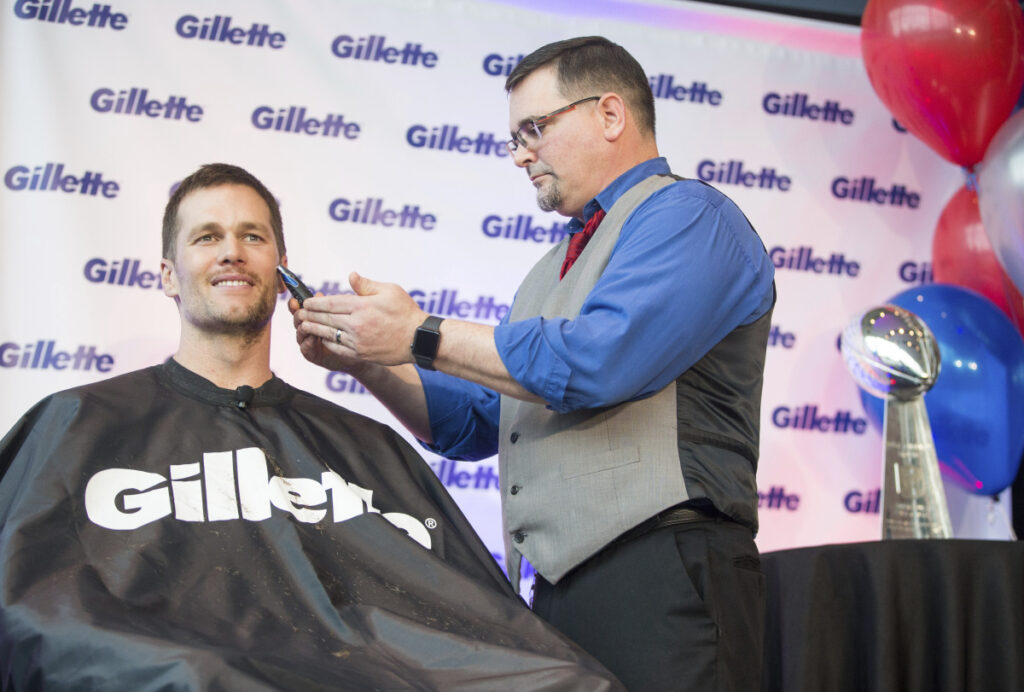New England Patriots quarterback Tom Brady parted with his playoff stubble and signed Gillette razors to benefit charities on Thursday.