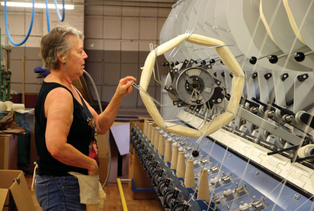 Inside Jagger Brothers worsted mill in Springvale, Ansie Stuart tends the machine that spins a hank of yarn onto a cone in 2016. Owner David Jagger said Friday that the manufacturing division will cease operations, likely by the end of March.