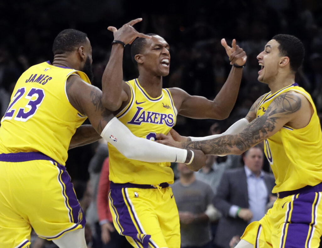 Rajon Rondo of the Los Angeles Lakers, center, celebrates with LeBron James, left, and Kyle Kuzma after hitting a winning shot Thursday night against Boston.