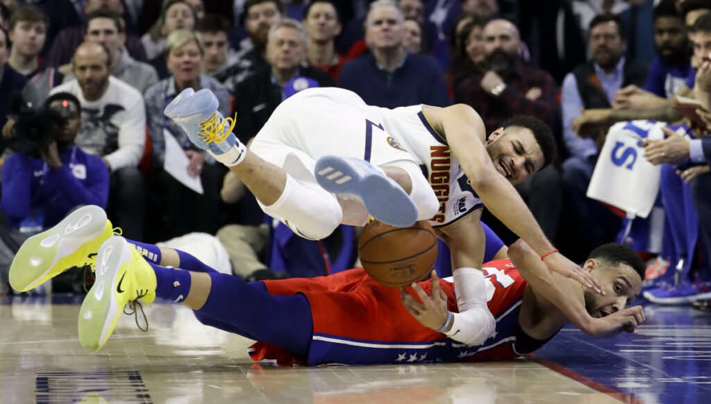 Jamal Murray of the Denver Nuggets, top, and Ben Simmons of the Philadelphia 76ers chase a loose ball Friday night during the first half of Philadelphia's 117-110 victory at home.