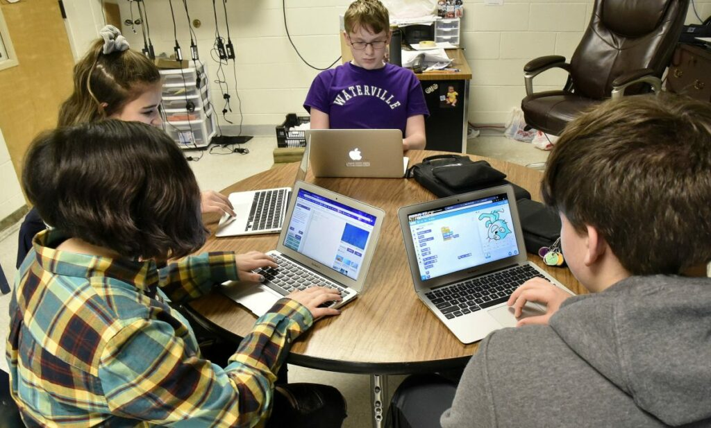 Morning Sentinel photo by David Leaming   Waterville Junior High School students, clockwise from lower left, Alexa DeWitt, Leilani Gomez, Zachary London and Dylan Mitchell, work on assignments with computers Thursday. When they move up to Waterville Senior High School, they will have the opportunity to participate in a unique computer science pilot program funded by an $881,000 grant from the Harold Alfond Foundation.