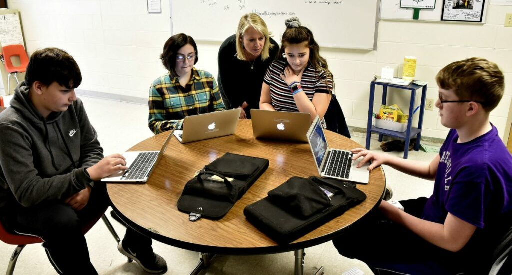 Kim Quinn Hutchinson, executive director of a computer science pilot program funded by an $881,000 grant from the Harold Alfond Foundation, assists Waterville Junior High School students, from left, Dylan Mitchell, Alexa DeWitt, Leilani Gomez and Zachary London.