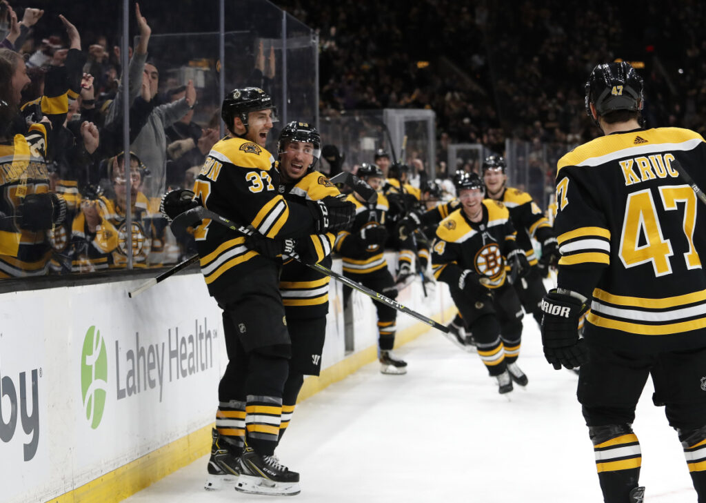 The Bruins stream onto the ice to celebrate after Patrice Bergeron, left, scored the game-winning goal in overtime to give Boston a 5-4 win over the Los Angeles Kind on Saturday in Boston.