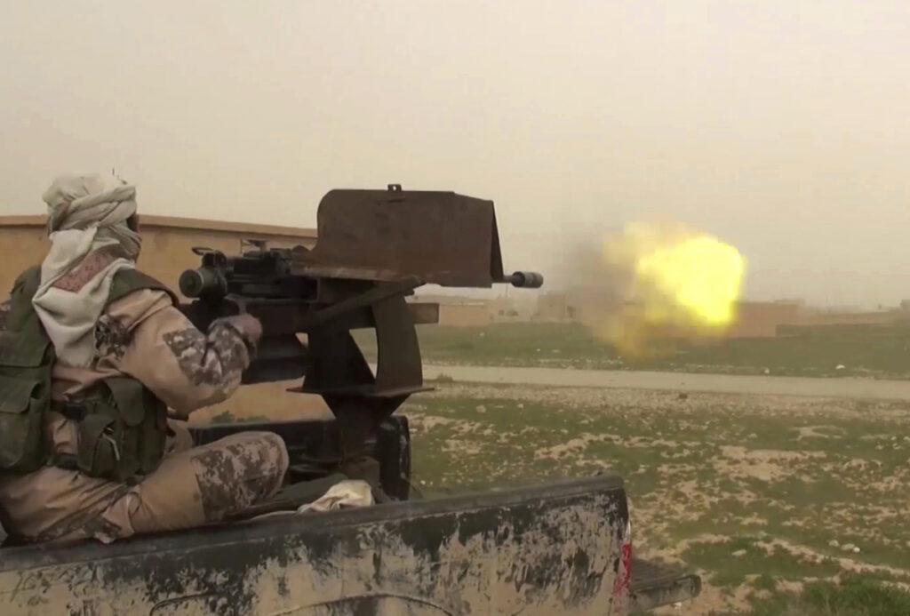 This frame grab from video posted online by supporters of the Islamic State purports to show a gun-mounted IS vehicle firing at members of the U.S.-backed Syrian Democratic Forces in the eastern province of Deir el-Zour in Syria.