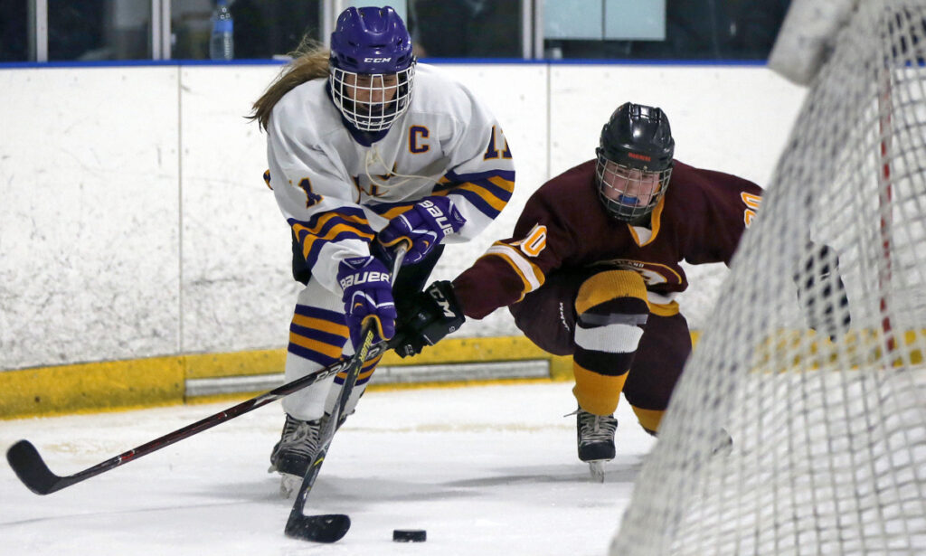 Sophia Pompeo, left, of Cheverus/Kennebunk/Old Orchard Beach tries to skate past Abbey Agrodnia of Cape Elizabeth/Waynflete/South Portland during Saturday's regional semifinal. Sophia's sister, Lucia, scored the game's only goal 1:27 into the second overtime.