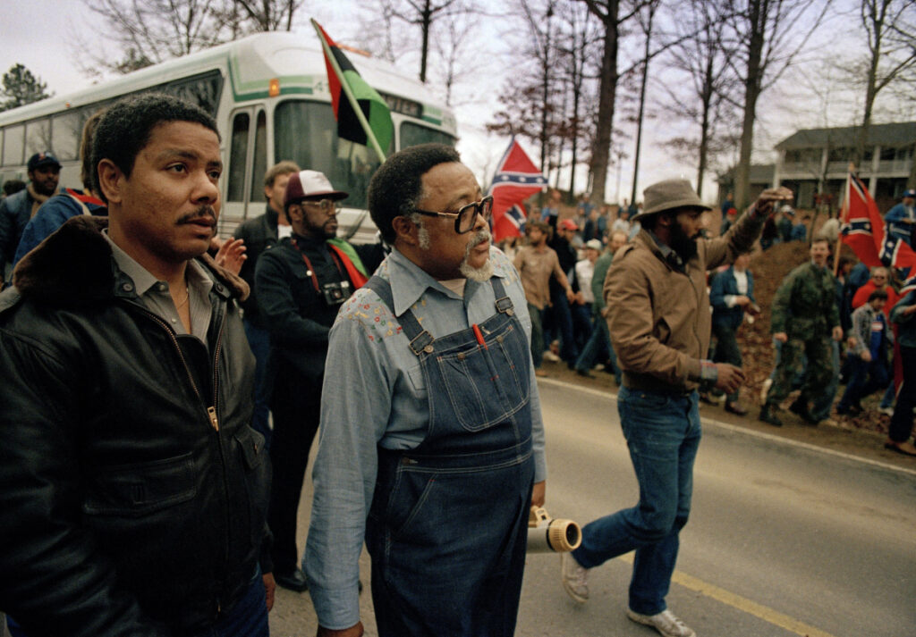 In this Jan. 18, 1987, photo, Atlanta city councilman, Rev. Hosea Williams, in overalls, leads a march against efforts to keep Forsyth County in Georgia all white past counter-protesters near Cumming, Ga., as a crowd waves Confederate flags and jeer the marchers. Racial stereotypes and racist imagery in popular culture seemed to be everywhere in the chaotic 1980s when future Virginia Gov. Ralph Northam and future Attorney General Mark Herring admitted dressing up in blackface.