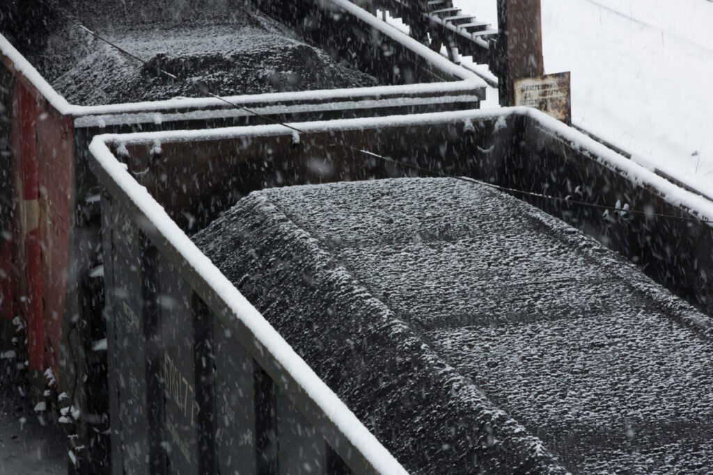 Snow falls on coal sitting in a freight wagon ahead of shipping at the dressing mill at the Sibir coal processing plant operated by OAO Mechel Mining, a unit of OAO Mechel, near Myski, Kemerovo region, Russia. MUST CREDIT: Bloomberg photo by Andrey Rudakov