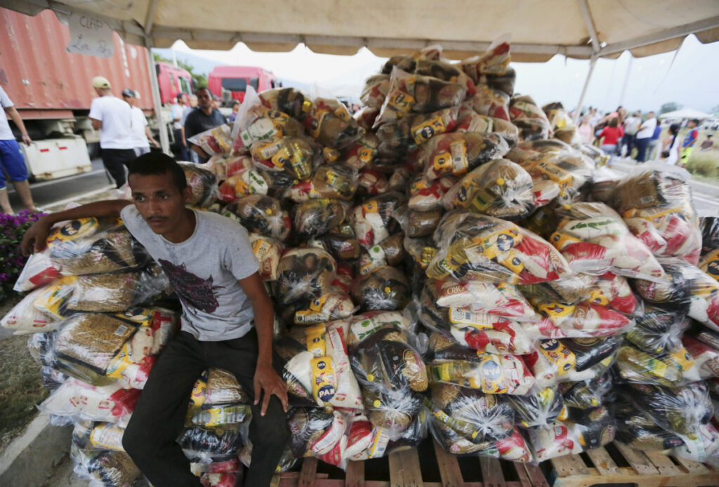 A volunteer takes a break during the distribution of bags with food subsidized by Nicolas Maduro's government near the international bridge of Tienditas on the outskirts of Urena, Venezuela.