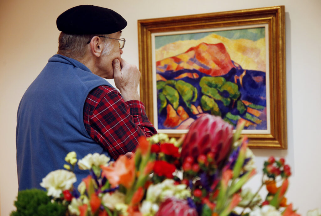 "PORTLAND, ME - FEBRUARY 13: George Viles of Cape Elizabeth studies an oil on canvas painting ""Unititled (Mont Sainte Victoire), circa 1925 by Marsden Hartley during a tour of Art in Bloom at Portland Museum of Art. The painting inspired the floral design by John Sundling of Plant Office. (Staff photo by Derek Davis/Staff Photographer)"