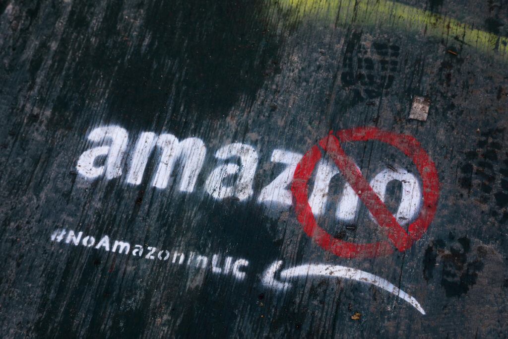 FILE- In this Nov. 16, 2018, file photo Graffiti was painted on a sidewalk by someone opposed to the location of an Amazon headquarters in the Long Island City neighborhood in the Queens borough of New York iin this 2018 photo. Amazon said Thursday that it will not build a new headquarters in New York, a stunning reversal after a yearlong search.
