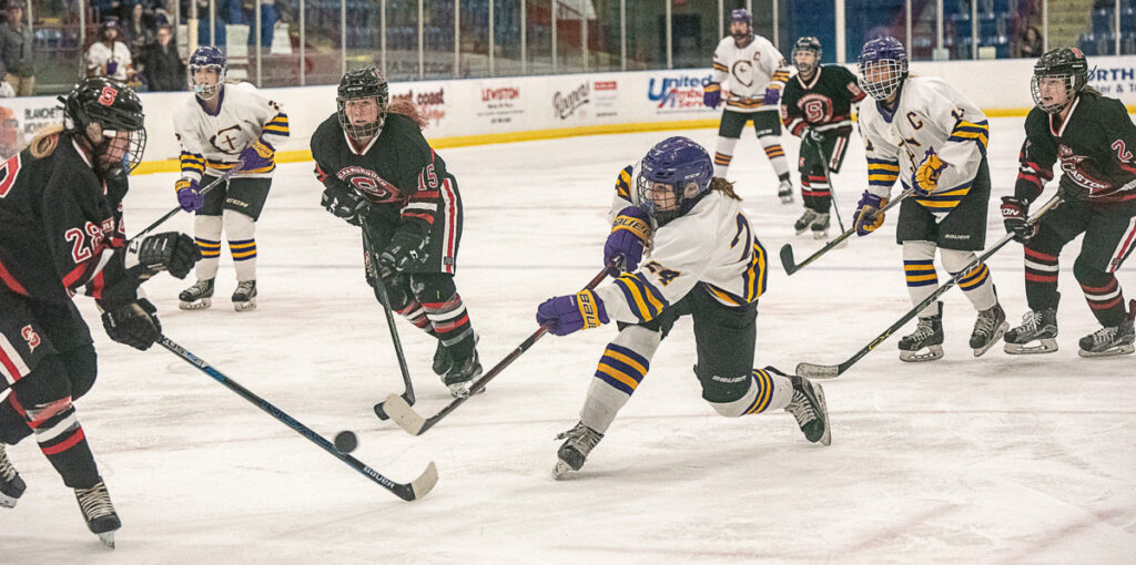 Abby Lamontagne of Cheverus/Kennebunk/Old Orchard Beach takes a shot while defended by Scarborough's Maya Sellinger, left, during the girls' hockey South final Thursday night in Lewiston. Cheverus won in overtime, 3-2.