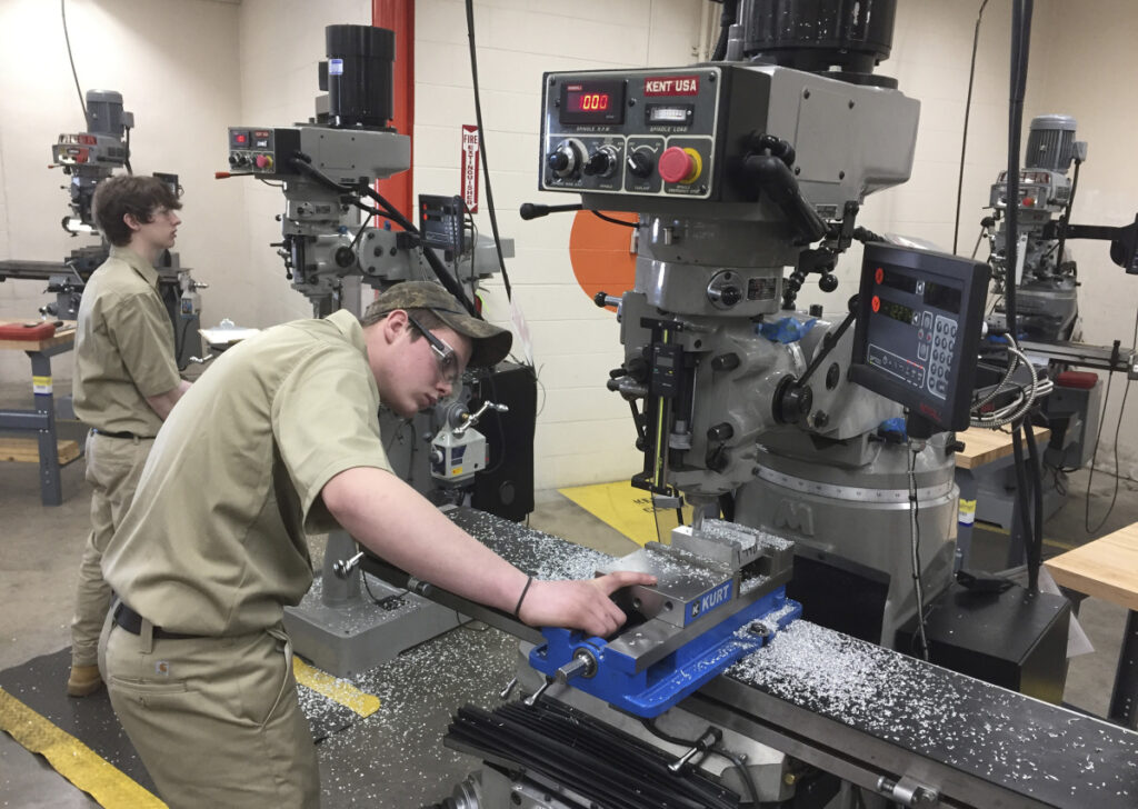 Cameron Etheridge, 18, of Dexter checks his work on a precision milling machine Thursday at SMCC.